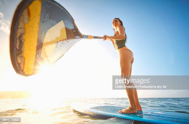 Mixed Race woman holding paddle on paddleboard in ocean