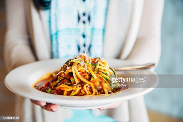 mixed race woman holding plate of pasta - texas bowl stock photos and pictures
