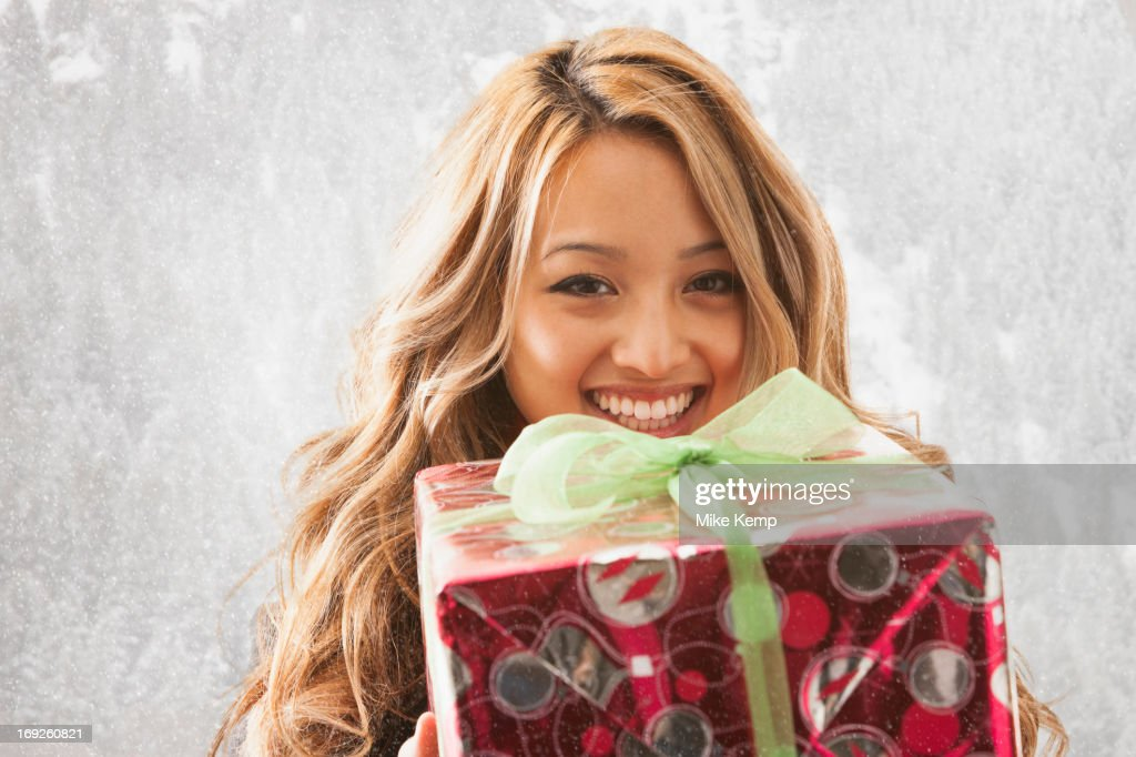Mixed race woman holding present in snow : Stock Photo