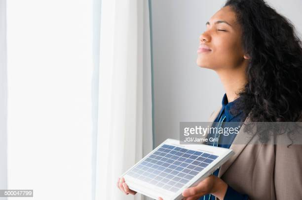 Mixed race woman holding solar panel by window