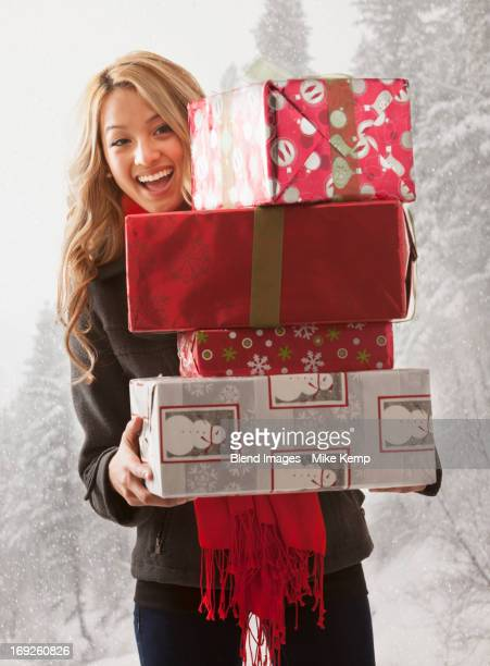 Mixed race woman holding stack of presents in snow