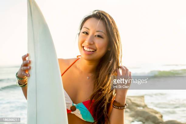 Mixed race woman holding surfboard on beach