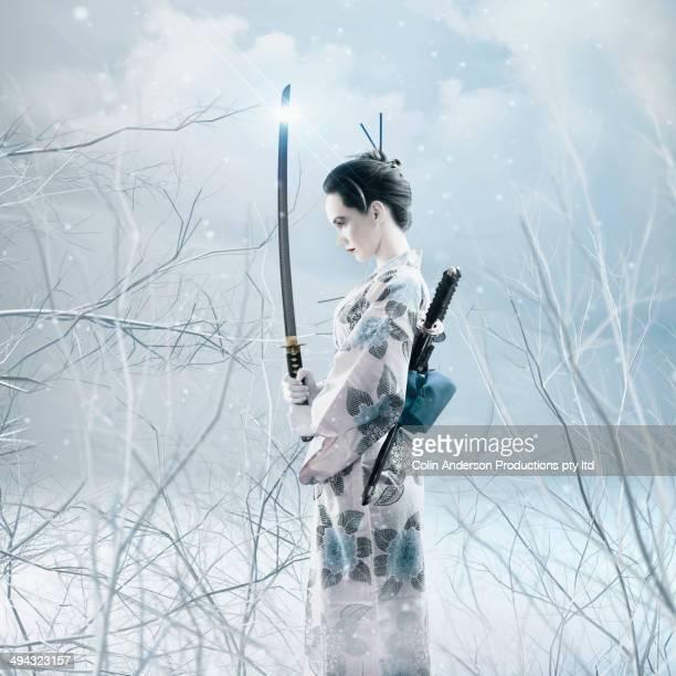 Mixed race woman holding sword in kimono