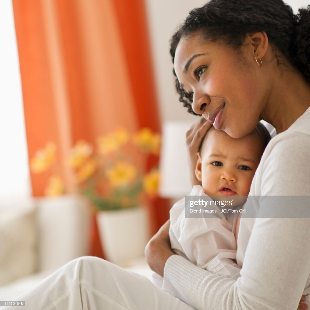 Mixed race woman hugging baby : Bildbanksbilder