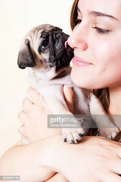 Mixed race woman hugging pug