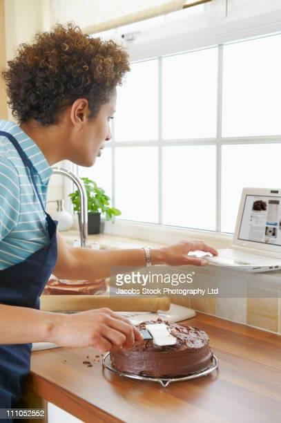 Mixed race woman icing cake