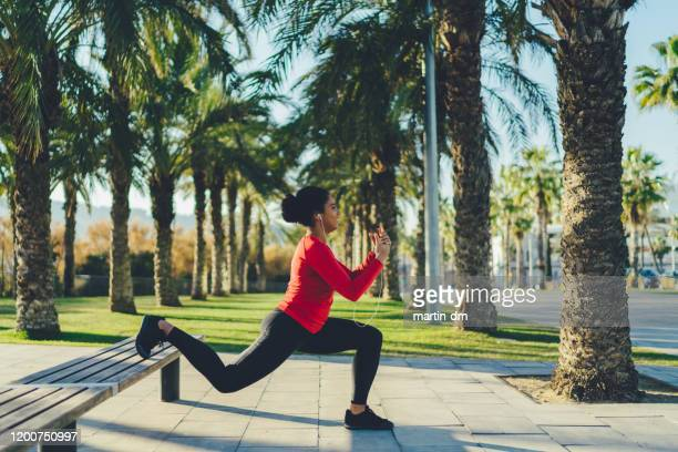 mixed race woman in barcelona exercising in the city - crouching stock pictures, royalty-free photos & images