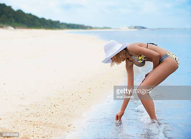 Mixed race woman in bikini picking up seashell on beach