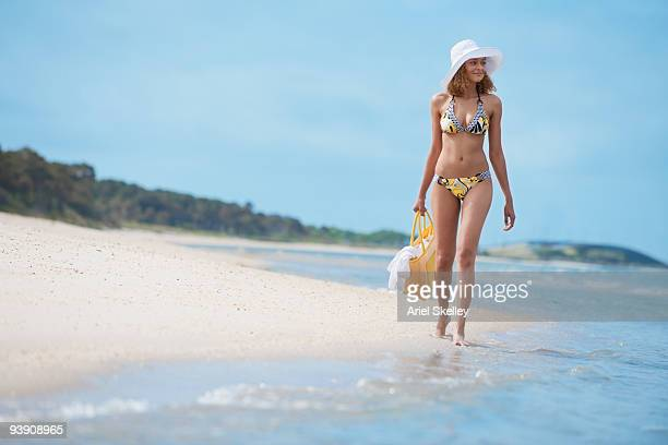 mixed race woman in bikini walking on beach - woman carrying tote bag stock photos and pictures