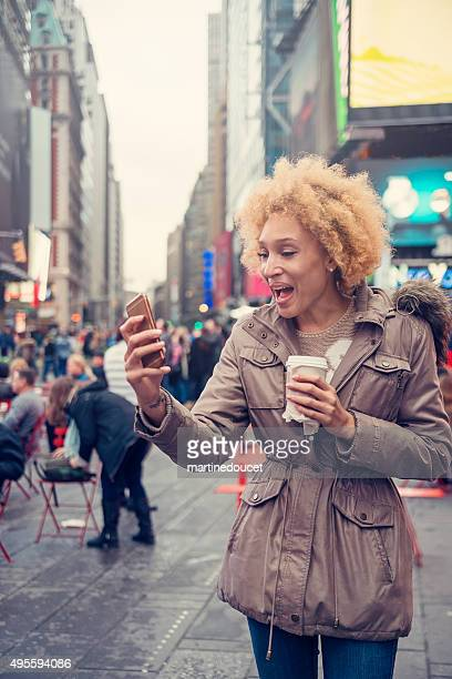 Mixed race woman in city street skype-ing on mobile phone.
