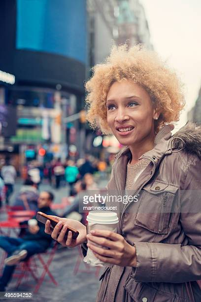"""mixed race woman in city street texting on mobile phone. - """"martine doucet"""" or martinedoucet stock pictures, royalty-free photos & images"""