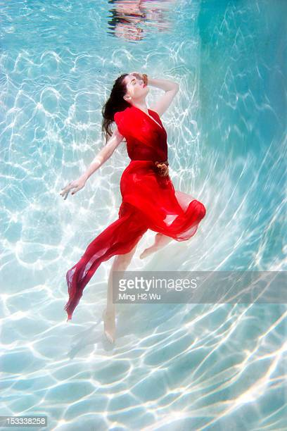 Mixed race woman in dress underwater in swimming pool