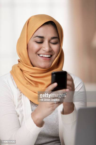 Mixed race woman in hijab text messaging on cell phone