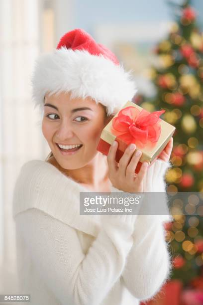 Mixed race woman in santa hat shaking Christmas present
