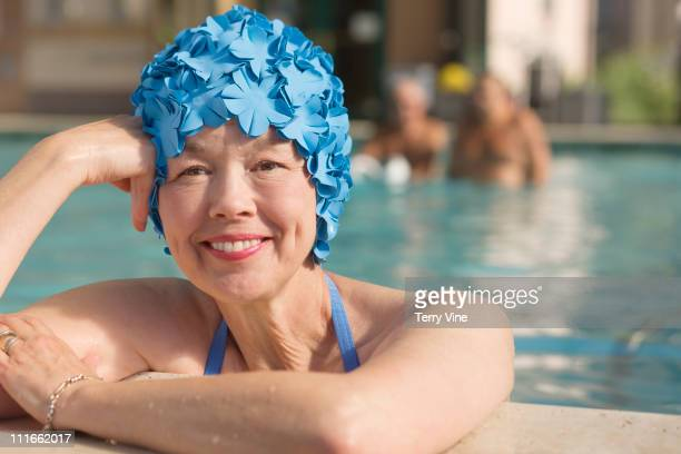 Mixed race woman in swimming pool wearing retro swimming cap