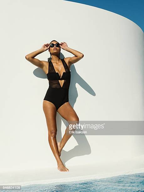 Mixed race woman in swimsuit wearing sunglasses near swimming pool