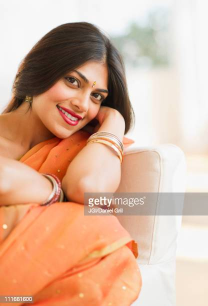 mixed race woman in traditional indian clothing sitting in chair - beautiful east indian women fotografías e imágenes de stock