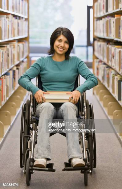Mixed Race woman in wheelchair at library