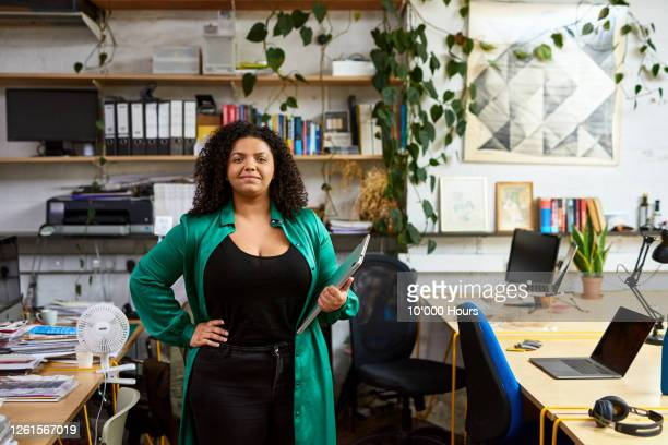 mixed race woman in workplace, hand on hip - new business stock pictures, royalty-free photos & images