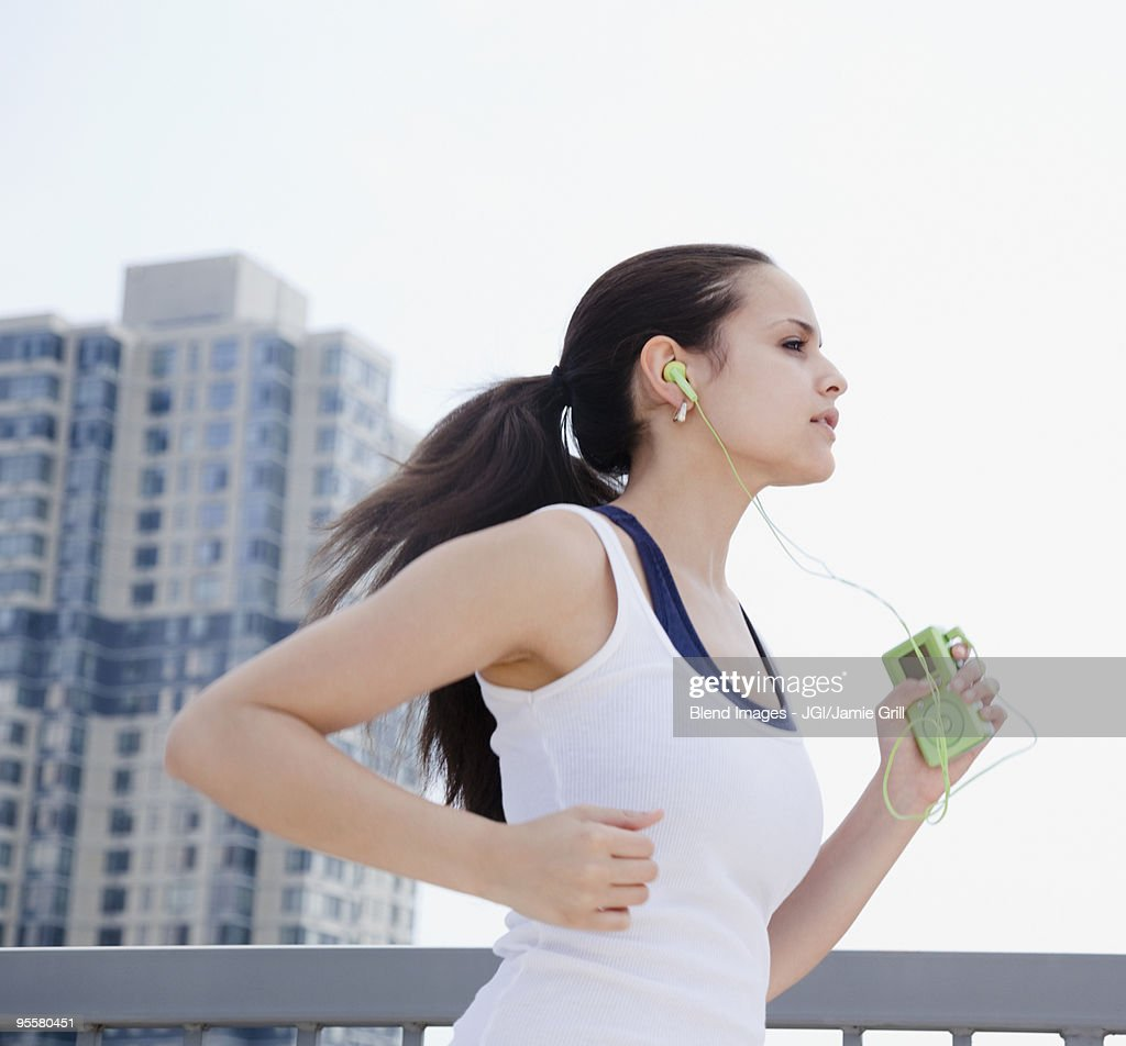 Mixed race woman jogging with mp3 player : Bildbanksbilder