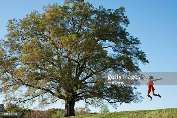 Mixed Race woman jumping for joy near tree