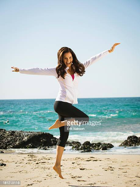 Mixed race woman jumping for joy on beach