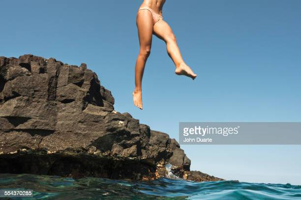 Mixed race woman jumping from rocks into ocean