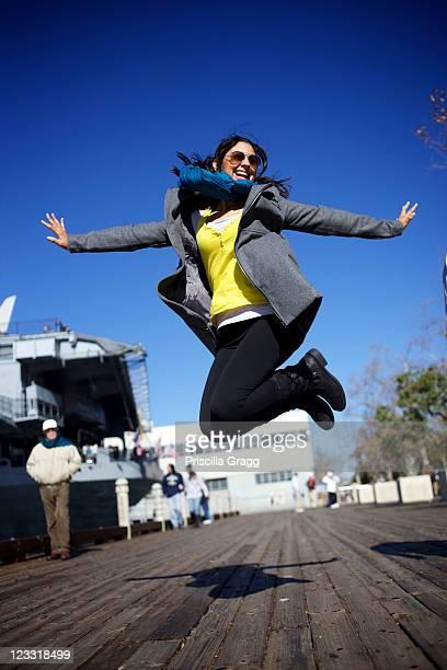 Mixed race woman jumping on boardwalk