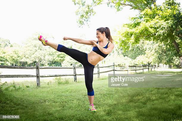Mixed race woman kicking in grass