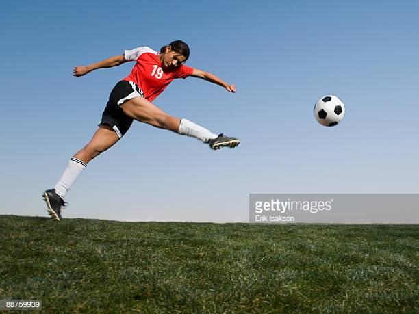 mixed race woman kicking soccer ball - donner un coup de pied photos et images de collection