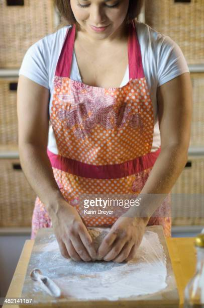Mixed race woman kneading dough in kitchen