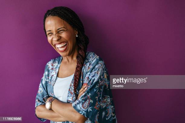 mixed race woman laughing with crossed arms - toothy smile stock pictures, royalty-free photos & images