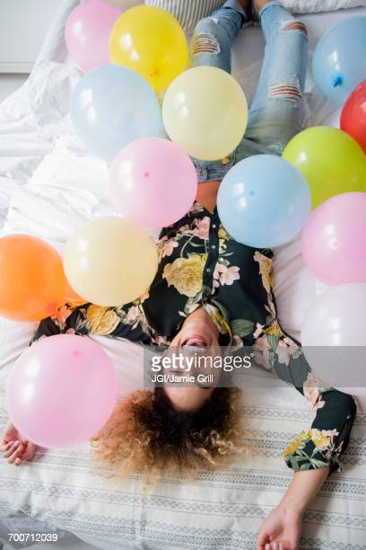 Funny birthday images free stock photos and pictures getty images mixed race woman laying on bed covered with balloons voltagebd Gallery