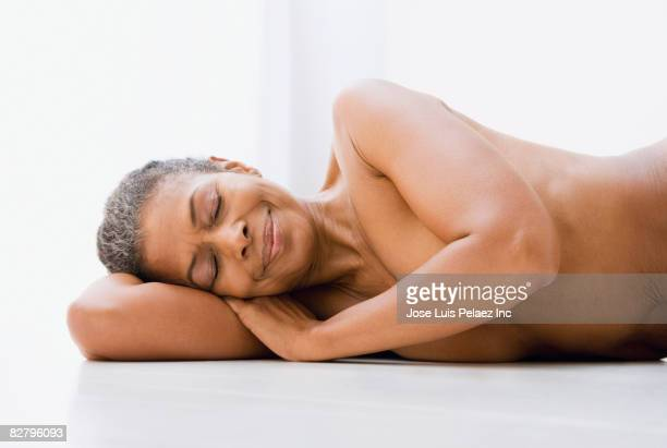 Mixed race woman laying on floor naked with eyes closed
