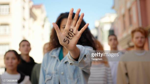 mixed race woman leader at protest showing hand with word stop. anti racism march demonstration - campaigner stock pictures, royalty-free photos & images