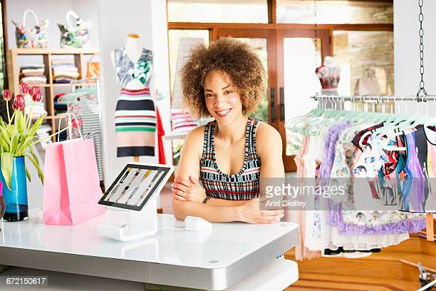 Mixed Race woman leaning on counter in clothing store