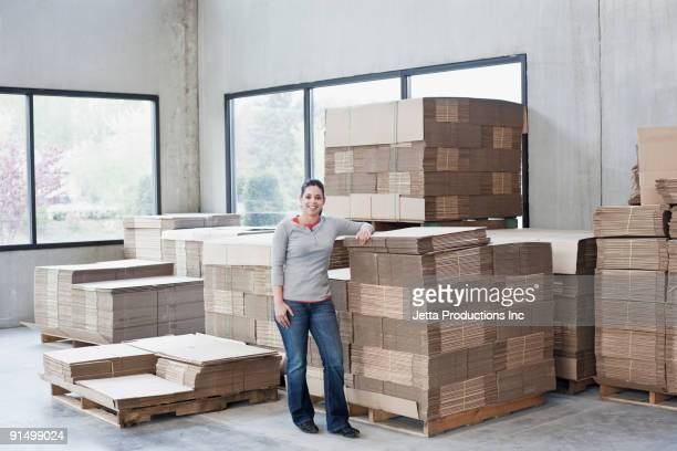 Mixed race woman leaning on flattened boxes in warehouse