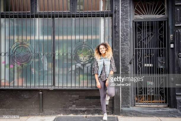 Mixed Race woman leaning on gated window in city