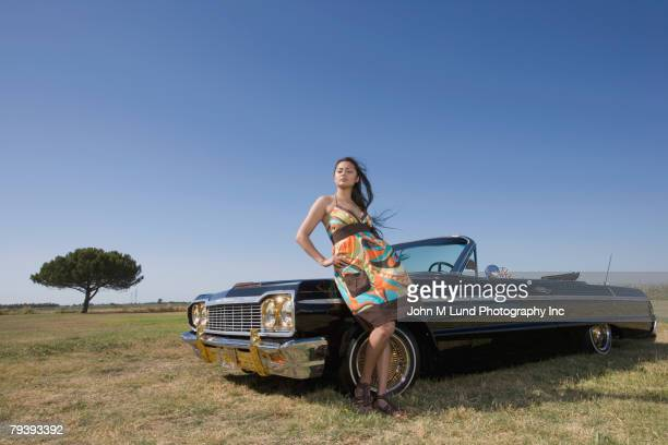 mixed race woman leaning on low rider car - low rider stock pictures, royalty-free photos & images
