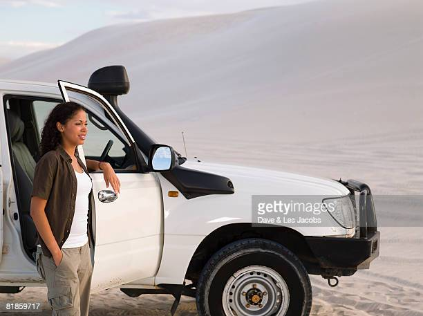 Mixed Race woman leaning on truck door