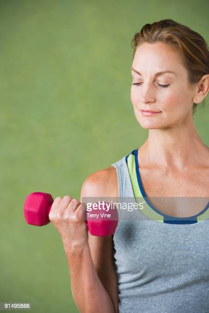 mixed race woman lifting hand weight - hand weight stock pictures, royalty-free photos & images
