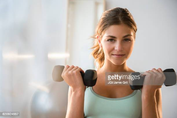 mixed race woman lifting weights in gym - haltere - fotografias e filmes do acervo
