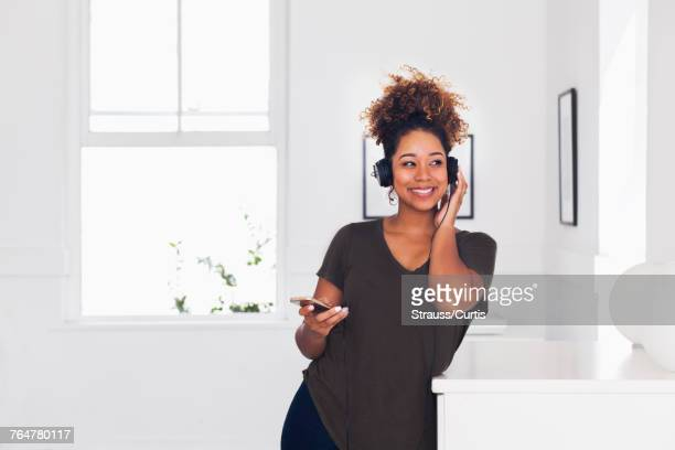 Mixed race woman listening to cell phone with headphones
