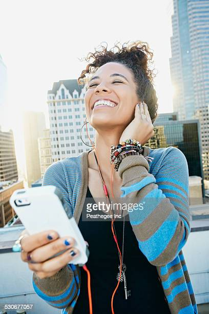 Mixed race woman listening to earbuds on urban rooftop
