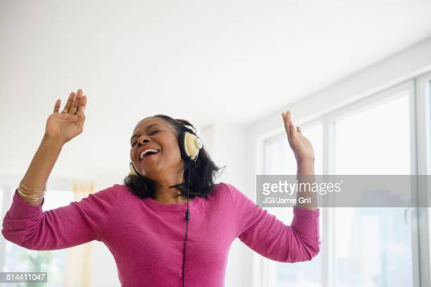 Mixed race woman listening to headphones in living room