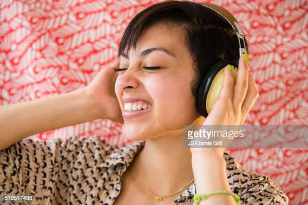 Mixed race woman listening to headphones