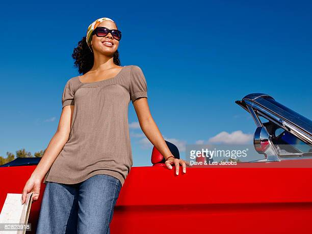 Mixed race woman looking at map near red convertible