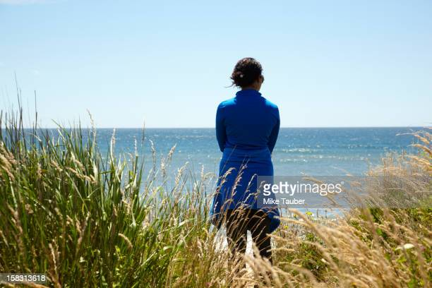 Mixed race woman looking at ocean