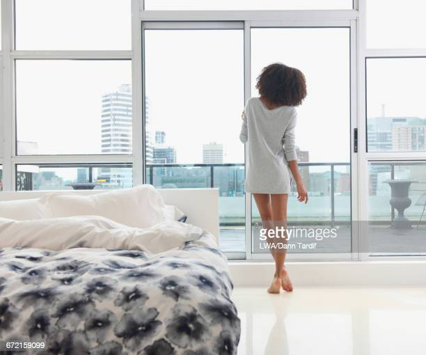 Mixed Race woman looking out bedroom window