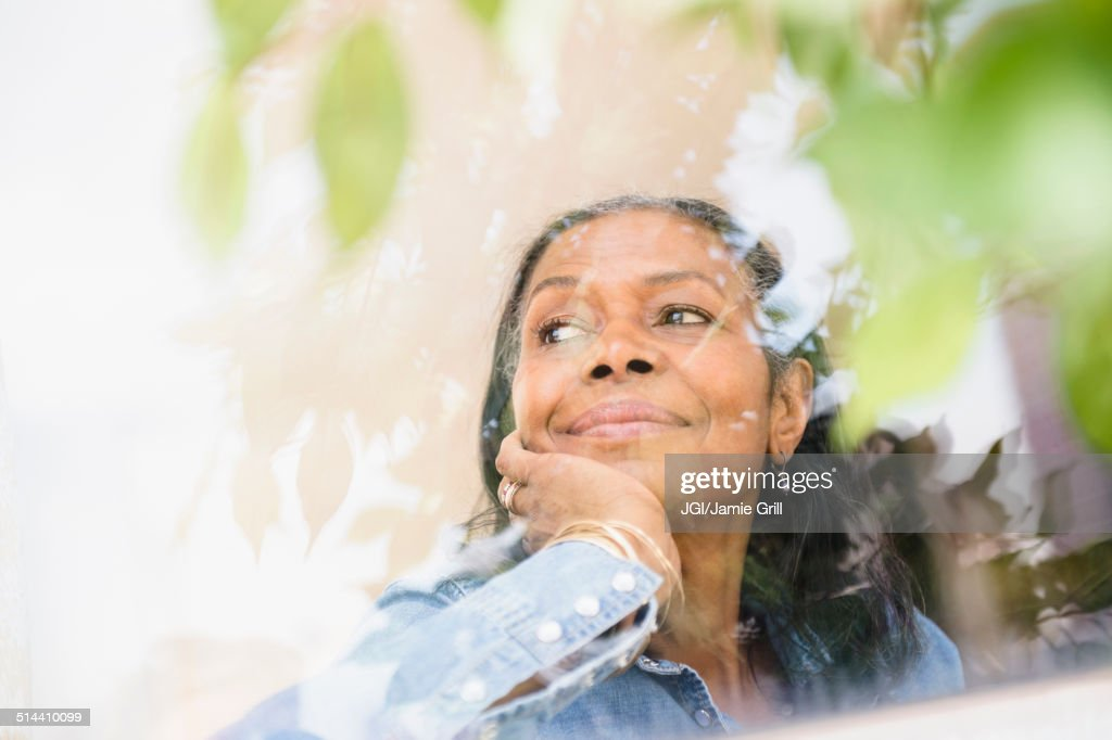 Mixed race woman looking out window : Stock Photo